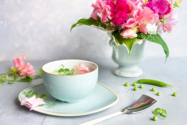 Zelfgemaakte verse doperwtenroomsoep met erwtenspruiten en bloemen