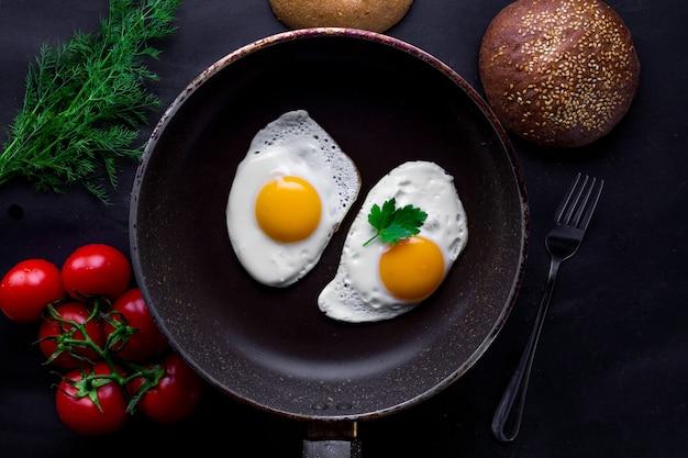 Zelfgemaakte, verse, gebakken eieren in een koekenpan met dille, peterselie, tomaten en sesambroodje voor een gezond ontbijt. bovenaanzicht eiwit eten
