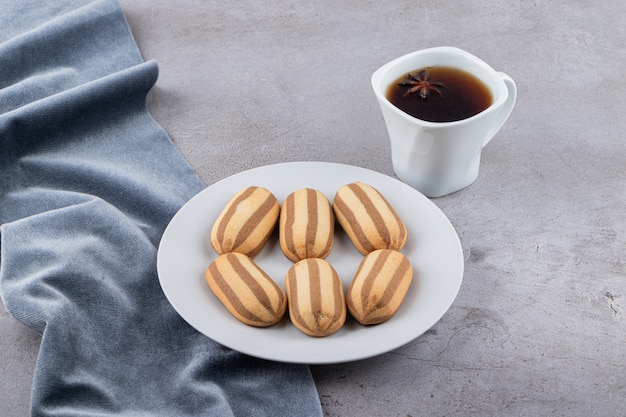 Zelfgemaakte verse koekjes met kopje geurige thee op grijs oppervlak