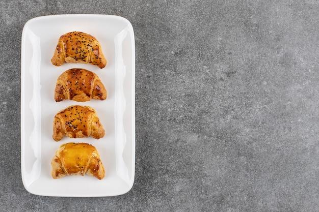 Zelfgemaakte verse koekjes op een rij op witte plaat