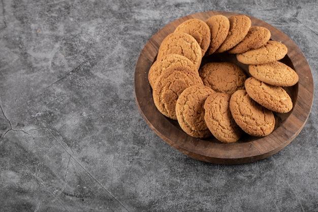 Zelfgemaakte verse koekjes op houten dienblad over grijze tafel.