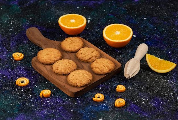 Zelfgemaakte verse koekjes op houten snijplank en half gesneden sinaasappels.