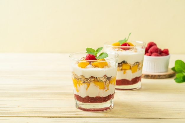Zelfgemaakte verse mango en verse framboos met yoghurt en granola - gezonde voeding
