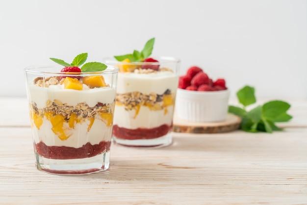 Zelfgemaakte verse mango en verse framboos met yoghurt en granola - healthy food style