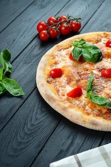 Zelfgemaakte verse pizza margherita met rode saus, basilicum en cherrytomaat op een zwarte houten met kopie ruimte.