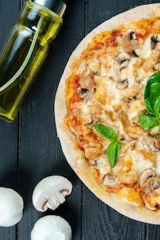 Zelfgemaakte verse pizza met gerookte kip, champignons, basilicum en witte saus op een zwarte houten met kopie ruimte.