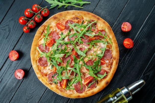 Zelfgemaakte verse pizza met salami, cherrytomaatjes en rucola op een zwarte houten met kopie ruimte. bovenaanzicht eten foto.