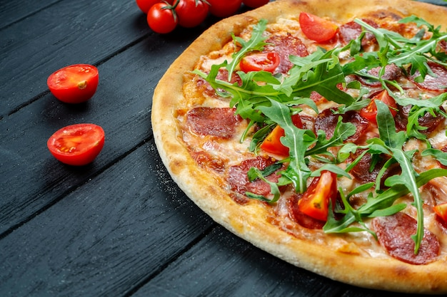 Zelfgemaakte verse pizza met salami, cherrytomaatjes en rucola op een zwarte houten met kopie ruimte.