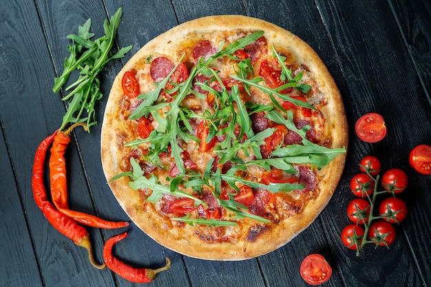Zelfgemaakte verse pizza met salami, peperoni cherrytomaatjes en rucola op een zwarte houten met kopie ruimte.