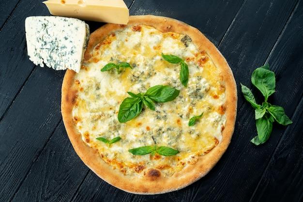 Zelfgemaakte verse pizza met vier kaas en basilicum op een zwarte houten met kopie ruimte. bovenaanzicht eten foto. plat liggen. italiaanse keuken.