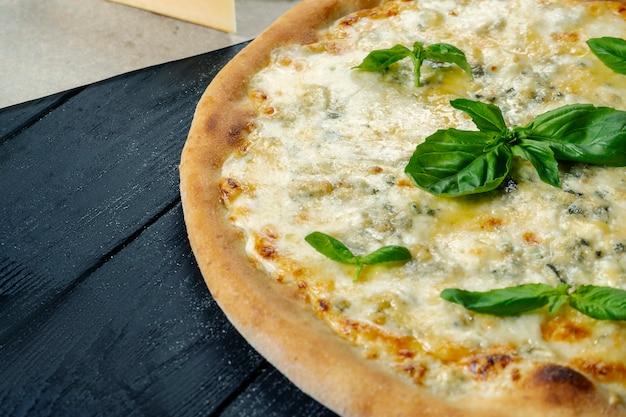Zelfgemaakte verse pizza met vier kaas en basilicum op een zwarte houten met kopie ruimte. bovenaanzicht eten foto.