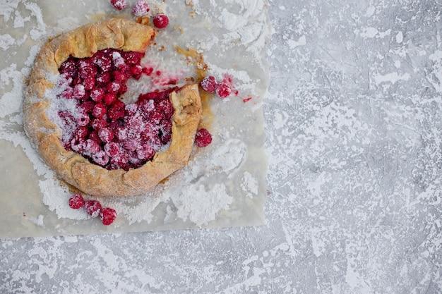 Zelfgemaakte vlaai galette gemaakt met verse frambozen met poedersuiker op concrete achtergrond. open taart, frambozentaart. zomer berry dessert. plat leggen.