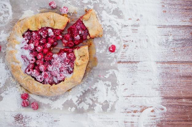 Zelfgemaakte vlaai galette gemaakt met verse frambozen met poedersuiker op houten tafel. open taart, frambozentaart. zomer berry dessert. plat leggen.