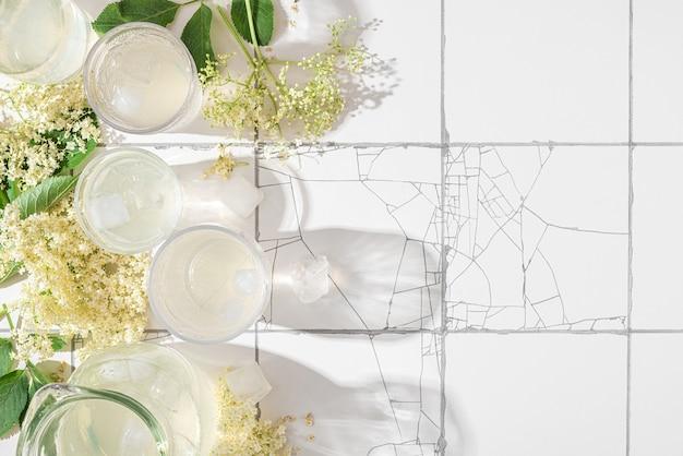 Zelfgemaakte vlierbloesemsiroop koude zomerdrank met ijsblokjes en verse vlierbloesem in glazen op witte tegeltafel