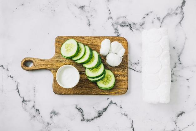 Zelfgemaakte vochtinbrengende crème; plakjes komkommer en katoen op snijplank met handdoek over de marmeren achtergrond