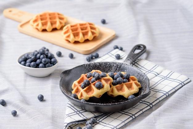 Zelfgemaakte wafels bosbessen en glazuur op een gerecht dat lijkt op een pan.