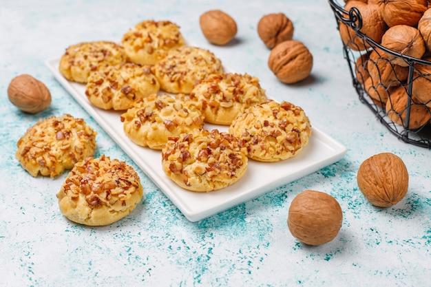 Zelfgemaakte walnoot cookies in witte plaat met walnoten op lichte tafel