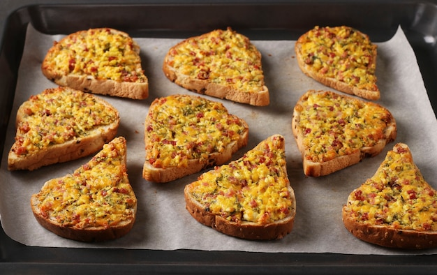 Zelfgemaakte warme broodjes met kaas en worst, op perkament op een bakplaat, horizontaal formaat, close-up