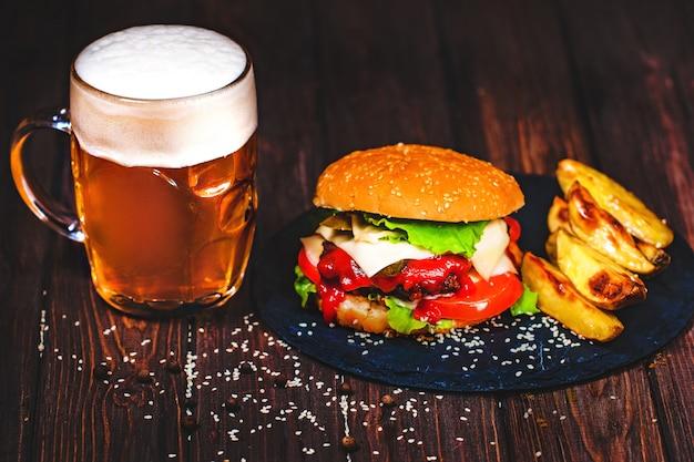 Zelfgemaakte watertanden, heerlijke rundvleesburger met sla en aardappel, glas bier geserveerd op stenen snijplank. donker