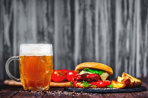 Zelfgemaakte watertanden, heerlijke rundvleesburger met sla en aardappel, glas bier geserveerd op stenen snijplank.