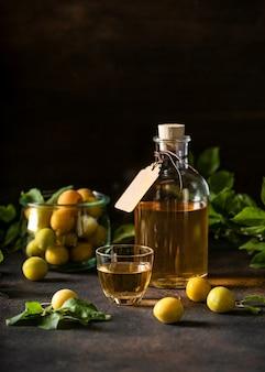 Zelfgemaakte wijn of likeur van gele kersenpruim in een klein glas en rijp fruit op donkere tafel
