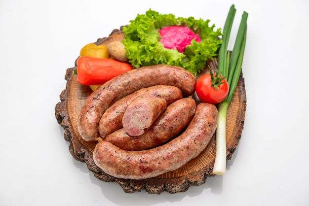Zelfgemaakte worst met groenten op een houten bord