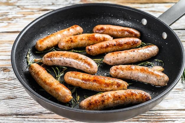 Zelfgemaakte worstjes gebakken in een pan, rundvlees en varkensvlees. houten achtergrond. bovenaanzicht.