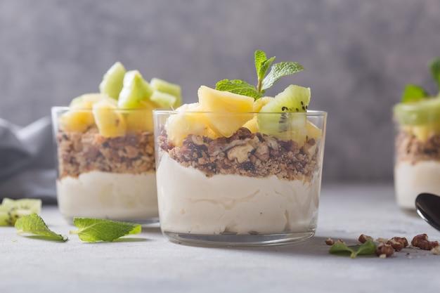 Zelfgemaakte yoghurt parfait met muesli, kiwi's, ananas en noten in een glas voor gezond ontbijt op concrete achtergrond