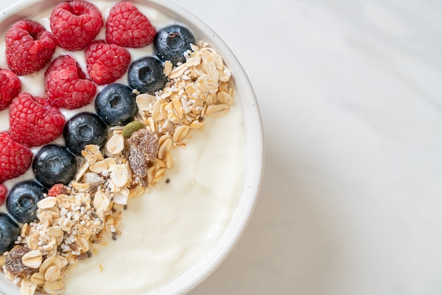 Zelfgemaakte yoghurtkom met framboos, bosbes en granola. gezonde voedingsstijl
