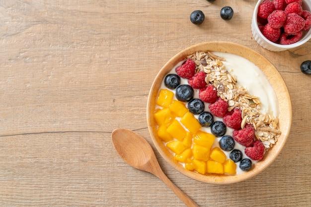 Zelfgemaakte yoghurtkom met framboos, bosbes, mango en granola - gezonde voedingsstijl