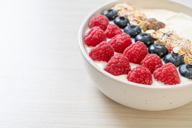 Zelfgemaakte yoghurtkom met frambozen, bosbessen en granola - gezonde voedingsstijl