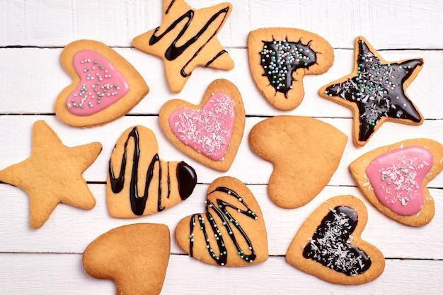 Zelfgemaakte zandkoekkoekjes, gekrulde koekjes met roze glazuur en chocolade. decoratieve koekjes op een wit