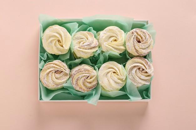 Zelfgemaakte zephyr of marshmallows in een doos op een roze achtergrond, horizontale oriëntatie, bovenaanzicht