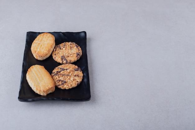 Zelfgemaakte zoete koekjes op houten plaat op marmeren tafel.