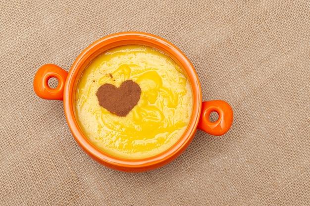Zelfgemaakte zoete maïspudding in brazilië bekend als curau of canjica nordestina in keramische kom