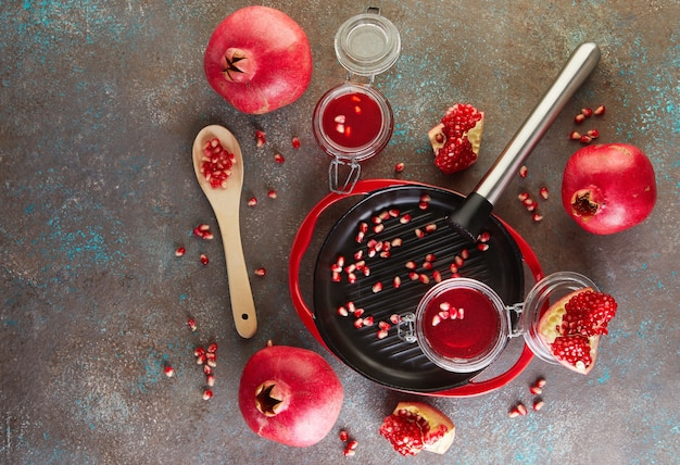 Zelfgemaakte zoete rode granaatappelsiroop in potten met granaatappelpitjes op een zwarte plaat met een rode rand