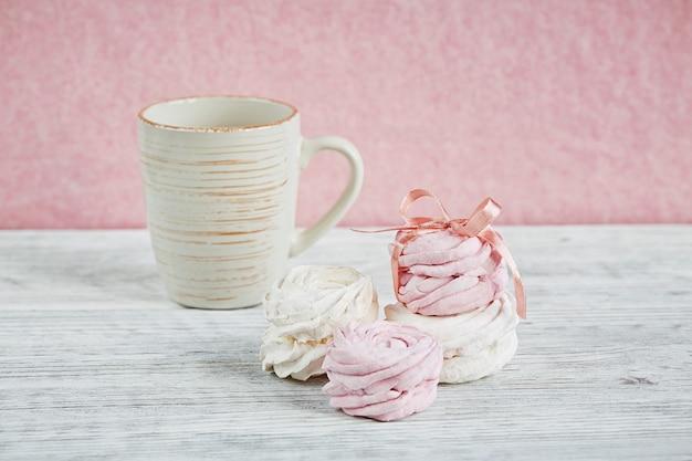 Zelfgemaakte zoete roze en witte marshmallow - zephyr op een lichte houten tafel.
