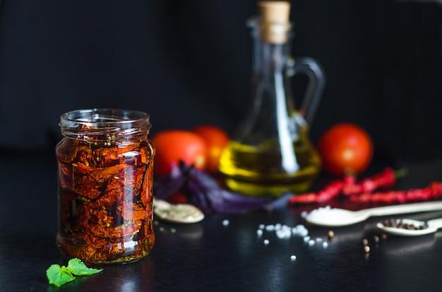Zelfgemaakte zongedroogde rode tomatenplakken in glazen pot met olijfolie, basilicum, oreganokruiden op donkere oppervlakte. kookproces traditionele italiaanse mediterrane keuken. kopieer ruimte, tekst