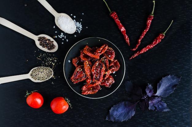 Zelfgemaakte zongedroogde rode tomatenplakken met olijfolie, zeezout, basilicum en oreganokruiden op donkere achtergrond. kookproces traditionele italiaanse mediterrane keuken. bovenaanzicht, plat leggen