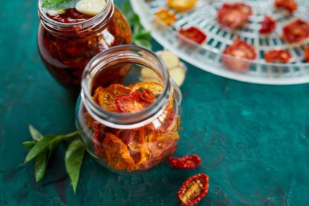 Zelfgemaakte zongedroogde tomaten met kruiden, knoflook in olijfolie in een glazen pot op donkergroene achtergrond. bovenaanzicht. afdrukken voor keuken