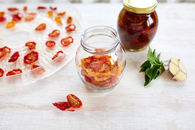 Zelfgemaakte zongedroogde tomaten met kruiden, knoflook in olijfolie in een glazen pot op witte houten achtergrond. bovenaanzicht. afdrukken voor keuken