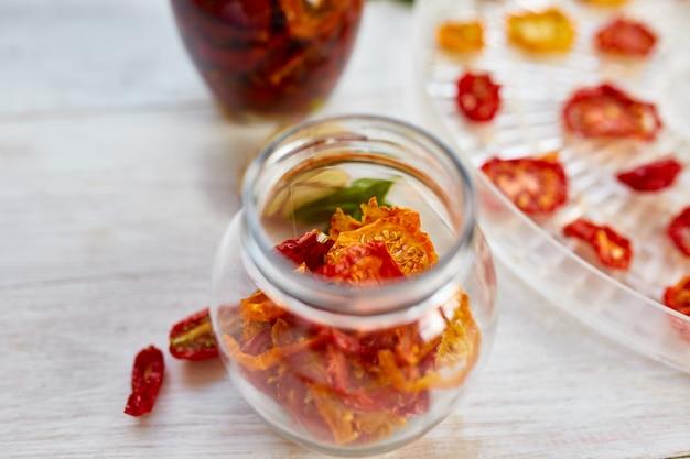 Zelfgemaakte zongedroogde tomaten met kruiden, knoflook in olijfolie in een glazen pot op witte houten achtergrond. kopieer de ruimte, close-up. afdrukken voor keuken.
