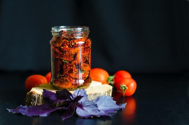 Zelfgemaakte zongedroogde tomatenplakken in glazen pot in olijfolie, basilicum, oreganokruiden, rode pomodoro op donkere achtergrond. traditionele italiaanse mediterrane keuken. kopieer ruimte, plaats voor tekst