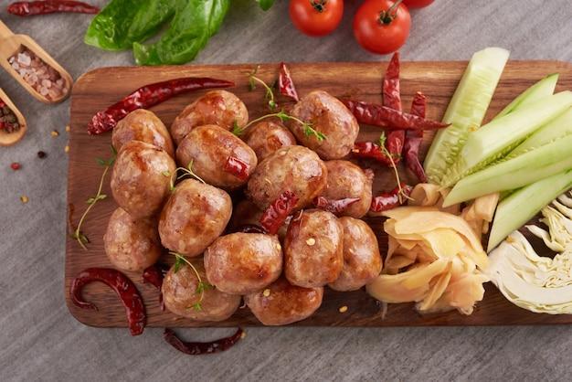 Zelfgemaakte zure worstjes met thaise kruiden, groenten. zelfgemaakte worstjes van varkensvlees in schil met kruiden en specerijen. bovenaanzicht.