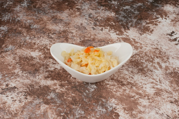 Zelfgemaakte zuurkool in een witte kom op marmeren tafel.