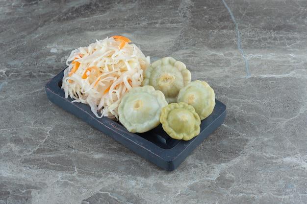 Zelfgemaakte zuurkool met groene patty pan squash op houten plaat.