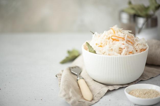 Zelfgemaakte zuurkool met wortelen en laurierblaadjes in een witte kom