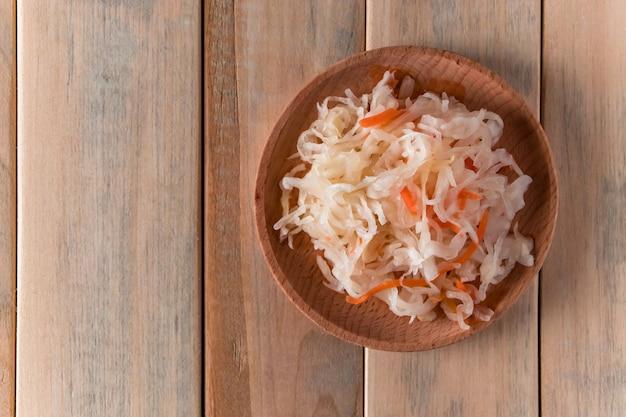 Zelfgemaakte zuurkool op een houten plaat. gefermenteerde kool met wortel op een lichte achtergrond
