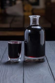 Zelfgemaakte zwarte appelbes wijn of likeur op zwarte houten oppervlak