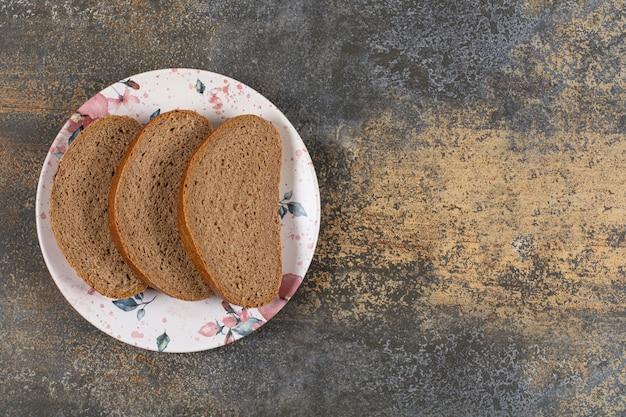 Zelfgemaakte zwarte broodplakken op kleurrijke plaat